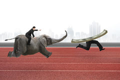 Man with pointing finger riding elephant running after money Royalty Free Stock Photo
