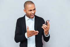 Man pointing with finger at smart phone grey background stock images