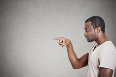 Man pointing with finger at something someone. Side profile young man pointing with finger at something someone on gray wall background Stock Image