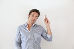 Man pointing finger at text on white wall Royalty Free Stock Image