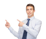 Man pointing finger to something on virtual screen. Business and office, advertising, people concept - friendly young buisnessman pointing finger to something on Royalty Free Stock Photos