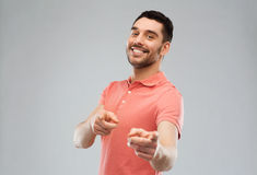 Man pointing finger to you over gray background Stock Images