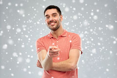 Man pointing finger to you over snow background Stock Images