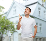 Man pointing finger up over house background Royalty Free Stock Images