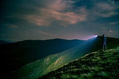 Searching with flashlight in mountains royalty free stock photography
