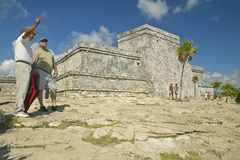 Man pointing in front of Mayan ruins of Ruinas de Tulum (Tulum Ruins) in Quintana Roo, Mexico. El Castillo is pictured in Mayan ru Royalty Free Stock Images