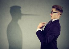 Man pointing at himself while lying. Side view of man in suit pointing at himself looking at shadow with long nose of a liar royalty free stock photos