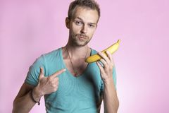 Man pointing his finger to a banana.  Royalty Free Stock Images