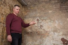 Man pointing with his hand and inviting you to join against the background of a peeling wall. Studio shoot Royalty Free Stock Photography