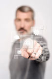 Man pointing icons on virtual screen Stock Images