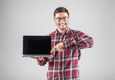 Man pointing on laptop. Smiling hipster pointing finger on blank laptop screen over gray background66 Stock Images