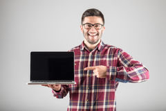 Man pointing on laptop. Smiling hipster pointing finger on blank laptop screen over gray background Royalty Free Stock Photography
