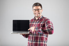 Man pointing on laptop. Smiling hipster pointing finger on blank laptop screen over gray background Royalty Free Stock Photo