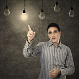 Man pointing at lit lightbulb Stock Photography