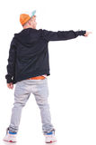 Man pointing & looking to side. Full length back view picture of a young man pointing and looking to his side, on white background Stock Photo