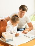 Man pointing on mistake at daughters notebook Royalty Free Stock Image