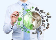 Man pointing at oil production and eco energy icons, environment. Man pointing at the brown picture of oil industry components and green eco energy arranged in Royalty Free Stock Photo