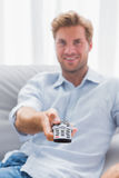 Man pointing remote control toward the camera Royalty Free Stock Images