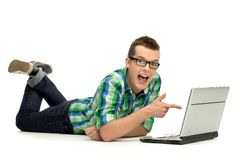 Man pointing at the screen of a laptop. Young man over white background Royalty Free Stock Images