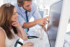Man pointing something to his partner on screen Stock Images