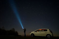 Man pointing at stars. Man pointing flashlight at sky full of stars at night stock photo