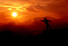 Man pointing at the sun. Sunset, clouds, silhouette, man, mountain, nature, horizon Royalty Free Stock Photos
