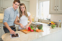Man pointing on tablet pc with woman chopping peppers Royalty Free Stock Photography