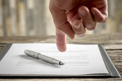 Man pointing to a document with a pen Stock Images