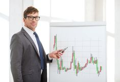 Man pointing to flip board with forex chart stock image