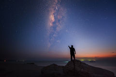 A man pointing to the milkyway. Milkyway rise above the South China Sea at Sabah Borneo Malaysia Royalty Free Stock Images