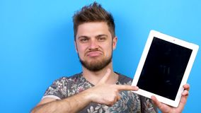 Man pointing to the screen of a digital tablet PC and shows thumb up. Shot on blue background. Slow motion footage. 4K resolution stock video footage