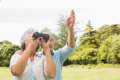 Man pointing to something for his wife holding binoculars Stock Photo