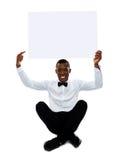 Man pointing towards blank billboard. Copyspace Stock Image