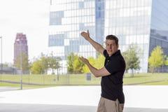 Man Pointing at Skyscraper Buildings. Man pointing towards skyscraper buildings in Frankfurt, Germany. Three quarter length Stock Photos