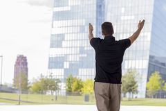 Man Pointing at Skyscraper Buildings Rear View. Man pointing towards skyscraper buildings in Frankfurt, Germany. Three quarter length. Rear view Stock Image
