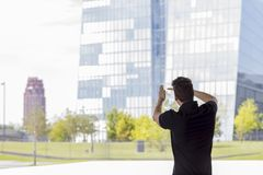 Man Pointing at Skyscraper Buildings Rear View. Man pointing towards skyscraper buildings in Frankfurt, Germany. Three quarter length. Rear view Stock Photography
