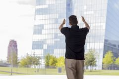 Man Pointing at Skyscraper Buildings Rear View. Man pointing towards skyscraper buildings in Frankfurt, Germany. Three quarter length. Rear view Royalty Free Stock Photos
