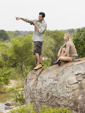 Man Pointing Towards View By Woman On Rock Royalty Free Stock Photo