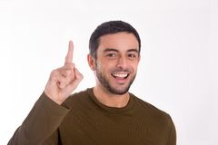 Man pointing up for copy space. Close up portrait of a man pointing up to copy space wearing a brown shirt and jeans on a white background Stock Photos