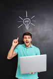 Man pointing up over blackboard background with drawn light bulb Stock Photos