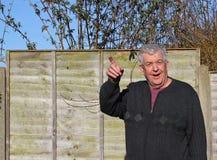 Man pointing upwards and looking towards camera. Royalty Free Stock Photography