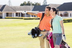 Man pointing while walking by woman carrying golf bag Stock Photos