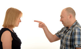 Man pointing at a woman. Side portrait of a man pointing accusingly at a woman with a white studio background Stock Photo