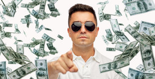 Man pointing on you with falling dollar money. Business, finance, gesture and people concept - face of middle aged latin man in sunglasses pointing finger on you Royalty Free Stock Images