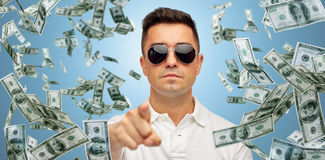 Man pointing on you with falling dollar money. Business, finance, gesture and people concept - face of middle aged latin man in sunglasses pointing finger on you Royalty Free Stock Image