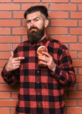 Man points at cocktail on brick wall background. Offer to drink concept. Barman with beard and inquiring face holds glass with cocktail straw. Hipster with Stock Photo