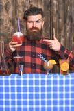 Man points at cocktail on wooden texture background. Offer to drink concept. Barman with beard and inquiring face holds glass with drinking straw cocktail Royalty Free Stock Photography