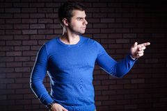 The man points the direction. Handsome young man in the blue jacket indicates the direction the finger Royalty Free Stock Photo