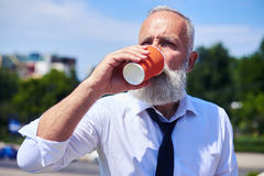 Man with poker face drinking coffee and enjoying panorama of cit Stock Image