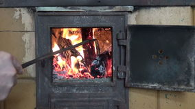 Man poking fire burning in old fireplace stock footage